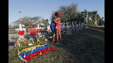 FILE - This Feb. 19, 2018 file photo shows Denyse Christian, hugging her son Adin Christian, 16, a student at the school, at a makeshift memorial outside the Marjory Stoneman Douglas High School, where 17 students and faculty were killed in a mass shooting in Parkland, Fla. Parkland city's historian Jeff Schwartz is setting a plan in motion to collect, archive and preserve the Marjory Stoneman Douglas mementos. Meanwhile, school administrators have vowed to build a memorial after the demolition of the building where the Feb. 14 attack took place. (AP Photo/Gerald Herbert, File)