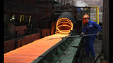 """In this March 5, 2018 photo, a worker manipulates coils of steel at Xiwang Special Steel in Zouping County in eastern China's Shandong province. China says it """"firmly opposes"""" U.S. President Donald Trump's tariff increase for imported steel and aluminum but gave no indication whether Beijing might impose its own measures in response. (Chinatopix via AP)"""