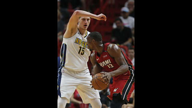 Miami Heat center Bam Adebayo (13) looks for an opening past Denver Nuggets  center Nikola Jokic (15) during the first half of an NBA basketball game,  ...