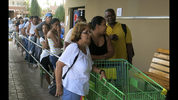 FILE - In this Sept. 25, 2017, file photo, people wait in line outside a grocery store to buy food that wouldn't spoil and that they could prepare without electricity, in San Juan. Emails and text messages made public March 20, 2018, show frantic efforts after Hurricane Maria by officials of the Puerto Rican government and Walmart to get fuel to keep their generators going _ and silence from the Federal Emergency Management Agency. A letter sent by the ranking member of the House oversight committee shows that as people stood in line for food and many went hungry, supermarkets were forced to throw out tons of spoiled meat, dairy and produce. (AP Photo/Ben Fox, File)