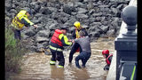 This photo from video provided by KSBY-TV shows rescuers bringing a man out of the muddy, rain-swollen Salinas River in Paso Robles on California's Central Coast Thursday, March 22, 2018. As of noon on Thursday, Paso Robles Fire Chief Jonathan Stornetta said five people had been rescued from the river, with two people taken to a hospital for treatment. A strong Pacific storm dropped record-breaking rain on a swath of California evacuated by thousands of people over threats of debris flows and mudslides from wildfire burn areas. (KSBY-TV via AP)