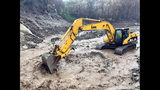 This photo provided by the Santa Barbara County Fire Department shows an excavator clearing boulders and debris from San Ysidro Basin in Montecito, Calif., Thursday, March 22, 2018 following heavy rains. Scars from the deadly Jan. 9 debris flow are still visible surrounding the basin and creek. (Mike Eliason/Santa Barbara County Fire Department via AP)