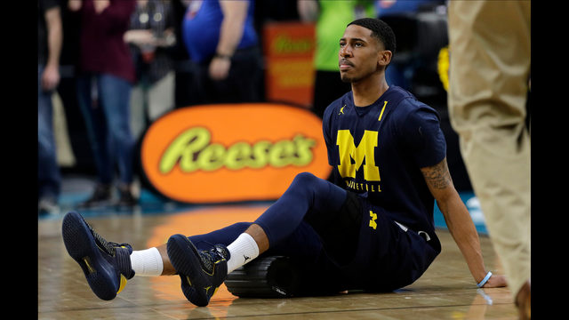 Michigan guard Charles Matthews stretches on the court during a practice  session for the Final Four NCAA college basketball tournament, Friday,  March 30, ...