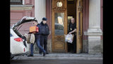 Men carry boxes and packs out from the U.S. consulate as a Russian police officer guards the entrance, in St.Petersburg, Russia, Friday, March 30, 2018. Russia announced the expulsion of more than 150 diplomats, including 60 Americans, on Thursday and said it was closing a U.S. consulate in retaliation for the wave of Western expulsions of Russian diplomats over the poisoning of an ex-spy and his daughter in Britain, a tit-for-tat response that intensified the Kremlin's rupture with the United States and Europe. (AP Photo/Dmitri Lovetsky)