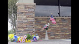 A memorial of with a flag and flowers sits in front of a restaurant window with bullet holes in Trenton, Fla., Friday, April 20, 2018. Authorities say two Florida sheriff's deputies were shot dead through the window of the Chinese restaurant by a man who then killed himself. (AP Photo/Jason Dearen)