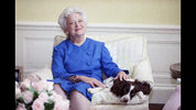 FILE - In this 1990 file photo, first lady Barbara Bush poses with her dog Millie in Washington. Barbara Bush, the snowy-haired first lady whose plainspoken manner and utter lack of pretense made her more popular at times than her husband, President George H.W. Bush, died Tuesday, April 17, 2018. She was 92. (AP Photo/Doug Mills, File)