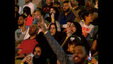 """Fans react as they watch the World Wrestling Entertainment Inc.'s """"Greatest Royal Rumble"""" event in Jiddah, Saudi Arabia, Friday, April 27, 2018. A previous WWE event held in the ultraconservative kingdom in 2014 was for men only. But Friday night's event in Jiddah included both women and children in attendance. (AP Photo/Amr Nabil)"""