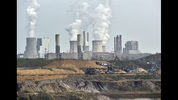 FILE - In this April 3, 2014 file photo giant machines dig for brown coal at the open-cast mining Garzweiler in front of a power plant near the city of Grevenbroich in western Germany. Allianz says it will stop insuring coal-fired power plants and coal mines as part of its contribution to combating climate change. (AP Photo/Martin Meissner, File)