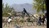 Students at Tuscano Elementary School play in the school playground as they wait for class to start as several Arizona schools resume classes Thursday, May 3, 2018, in Phoenix. After an all night legislative budget session the legislature passed the new education spending portion of the budget and Republican Gov. Doug Ducey signed that part of the budget. (AP Photo/Ross D. Franklin)