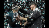 """FILE - In this Feb. 4, 2018 photo, Philadelphia Eagles quarterback Carson Wentz, right, hands the Vincent Lombardi trophy to Nick Foles after winning the NFL Super Bowl 52 football game against the New England Patriots in Minneapolis. The Eagles won 41-33. President Donald Trump has called off a visit by the Philadelphia Eagles to the White House Tuesday due to the dispute over whether NFL players must stand during the playing of the national anthem. Trump says in a statement that some members of the Super Bowl championship team """"disagree with their President because he insists that they proudly stand for the National Anthem, hand on heart."""" Trump says the team wanted to send a smaller delegation, but fans who planned to attend """"deserve better."""" (AP Photo/Frank Franklin II)"""