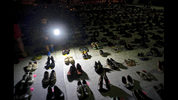 FILE - In this Friday, June 1, 2018 file photo, a child shines a light on hundreds of shoes at a memorial for those killed by Hurricane Maria, in front of the Puerto Rico Capitol in San Juan. In June 2018, two bills were introduced in Congress in an attempt to establish a new standard for counting deaths after a natural disaster. (AP Photo/Ramon Espinosa)