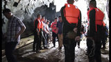 In this image made from video taken Sunday, June 24, 2018, rescue teams gather at the entrance of a deep cave where a group of boys went missing in Chang Rai, northern Thailand. Officials say multiple attempts to locate the 12 boys and their soccer coach missing in a flooded cave in northern Thailand for nearly two days have failed, but that they will keep trying. (TPBS via AP)