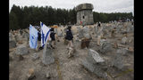 "FILE _ In this file photo dated Wednesday, Oct. 2, 2013, Israeli youths with their national flags march by the monument to some 900,000 European Jews killed by the Nazis between 1941 and 1944 at the Treblinka death and labor camp, at Treblinka memorial, Poland. Polish authorities have long argued they needed to fight back against foreign media sometimes calling German death camps ""Polish death camps"" because they were operated on occupied Polish territory. Poland's nationalist-conservative ruling party backed away Wednesday June 27, 2018, from a controversial Holocaust speech law, with prime minister Morawiecki introducing a new version of the law that would remove criminal provisions for statements deemed harmful to Poland's good name. (AP Photo/Czarek Sokolowski, FILE)"
