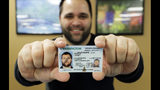 "Ryan Norris, a license service representative at the Washington state Dept. of Licensing office in Lacey, Wash., poses for a photo Friday, June 22, 2018 while holding a sample copy of a Washington drivers license. Some Washington licenses and identification cards will soon be marked with the words ""federal limits apply"" as the state moves to comply with a federal law that increased rules for identification needed at airports and federal facilities. (AP Photo/Ted S. Warren)"