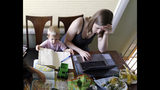 In this Wednesday, June 27, 2018, photo, Caely Barrett, who is part of a small group of stay-at-home mothers working to organize an immigration rally, works on her laptop next to her 18-month-old son in Portland, Ore. The small group of mothers organizing Saturday's rally in Portland to coincide with Families Belong Together rallies nationwide, are working almost around-the-clock to pull together an event expected to attract 5,000 people. (AP Photo/Don Ryan)