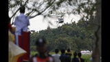 Locals watch a helicopter believed to be carrying one of the boys rescued from the flooded cave, lands in Chiang Rai as divers continue to extract the remaining boys and their coach trapped at Tham Luang cave in the Mae Sai district in Chiang Rai province, northern Thailand, Tuesday, July 10, 2018. Thai Navy SEALs say all 12 boys and their coach were rescued from the cave, ending an ordeal that lasted more than 2 weeks. (AP Photo/Vincent Thian)