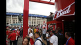 In this July 11, 2018 photo, people walk past a Budweiser pavilion in front of the Luzhniki Stadium as fans arrive for the semifinal match between Croatia and England, during the 2018 soccer World Cup in Moscow, Russia. (AP Photo/Rebecca Blackwell)