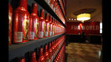 In this July 5, 2018 photo, Budweiser World Cup bottles line a wall in the lobby of the InterContinental Hotel, which has been taken over by Bud for the duration of the 2018 soccer World Cup, in Moscow, Russia. (AP Photo/Rebecca Blackwell)