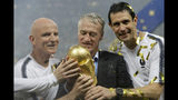 France head coach Didier Deschamps, second right, holds the trophy at the end of the final match between France and Croatia at the 2018 soccer World Cup in the Luzhniki Stadium in Moscow, Russia, Sunday, July 15, 2018. (AP Photo/Matthias Schrader)