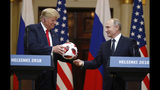 Russian President Vladimir Putin gives a soccer ball to U.S. President Donald Trump, left, during a press conference after their meeting at the Presidential Palace in Helsinki, Finland, Monday, July 16, 2018. (AP Photo/Alexander Zemlianichenko)