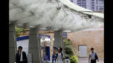 CORRECTS DATE - People cool down under the cooling mist spot in Tokyo, Monday, July 23, 2018. Searing hot temperatures are forecast for wide swaths of Japan and South Korea in a long-running heat wave. The mercury is expected to reach 39 degrees Celsius (102 degrees Fahrenheit) on Monday in the city of Nagoya in central Japan and reach 37 (99 F) in Tokyo. (AP Photo/Koji Sasahara)