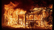 FILE - In this Thursday, July 26, 2018 file photo, a structure burns as the Carr fire races along Highway 299 near Redding, Calif. In the last year, fires have devastated neighborhoods in the Northern California wine country city of Santa Rosa, the Southern California beach city of Ventura and, now, the inland city of Redding. Hotter weather from changing climates is drying out vegetation, creating more intense fires that spread quickly from rural areas to city subdivisions, climate and fire experts say. But they also blame cities for expanding into previously undeveloped areas susceptible to fire. AP Photo/Noah Berger, File)