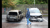 "A person walks past burned cars parked at Frolunda Square in Gothenburg, Tuesday, Aug. 14, 2018. Masked youth torched dozens of cars overnight in Sweden and threw rocks at police, prompting an angry response from the prime minister, who on Tuesday spoke of an ""extremely organized"" night of vandalism. (Adam Ihse/TT via AP)"
