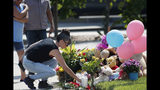 Irene Montoya of Aurora, Colo., places a bouquet of flowers as tributes grow outside the home where a pregnant woman and her two daughters lived Thursday, Aug. 16, 2018, in Frederick, Colo. The woman's husband has been arrested in the disappearance of the woman and children. Authorities say that they have found the woman's body and believe to know the whereabouts of the two girls. (AP Photo/David Zalubowski)