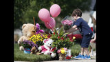 An unidentified young boy places a bouquet of flowers on a pile of tributes outside the home where a pregnant woman and her two daughters lived Thursday, Aug. 16, 2018, in Frederick, Colo. The woman's husband has been arrested in the disappearance of the woman and children. Authorities say that they have found the woman's body and believe to know the whereabouts of the two girls. (AP Photo/David Zalubowski)