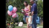 Ashley Bell, left, is consoled by her husband, Steven, and 4-year-old daughter Liberty as the woman places a tribute outside the home where a pregnant woman and her two daughters lived Thursday, Aug. 16, 2018, in Frederick, Colo. The woman's husband has been arrested in the disappearance of the woman and children. Authorities say that they have found the woman's body and believe to know the whereabouts of the two girls. (AP Photo/David Zalubowski)