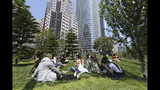 In this photo taken Wednesday, Aug. 15, 2018, employees from marketing company Linqia have a picnic lunch on the rooftop park of the new Transbay Transit Center in San Francisco. The new $2.2 billion center opened earlier this month. (AP Photo/Lorin Eleni Gill)