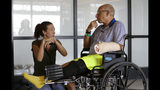 William Lytton, of Scarsdale, N.Y., right, speaks with physical therapist Caitlin Geary, left, during physical therapy at Spaulding Rehabilitation Hospital, in Boston, Tuesday, Aug. 28, 2018, while recovering from a shark attack. Lytton suffered deep puncture wounds to his leg and torso after being attacked by a shark on Aug. 15, 2018 while swimming off a beach, in Truro, Mass. Lytton injured a tendon in his arm while fighting off the shark. (AP Photo/Steven Senne)