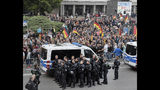 People are watched by police as they attend a demonstration in Chemnitz, eastern Germany, Friday, Sept.7, 2018, after several nationalist groups called for marches protesting the killing of a German man two weeks ago, allegedly by migrants from Syria and Iraq. (AP Photo/Jens Meyer)