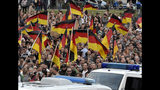 People wave with German national flags during a demonstration in Chemnitz, eastern Germany, Friday, Sept.7, 2018, after several nationalist groups called for marches protesting the killing of a German man two weeks ago, allegedly by migrants from Syria and Iraq. (AP Photo/Jens Meyer)
