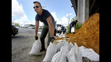 Kevin Orth loads sandbags into cars on Milford Street as he helps residents prepare for Hurricane Florence, Monday, Sept. 10, 2018, in Charleston, S.C. (Grace Beahm Alford/The Post And Courier via AP)
