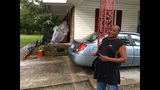 James Howell Jr. sizes up how to protect his home Tuesday, Sept. 11, 2018, in Princeville, N. C., from the approaching Hurricane Florence. The house was damaged by Hurricane Matthew in 2016. Howell said the furniture on his porch is there because he had to go out and rebuild the living room. (AP Photo/Emery Dalesio)