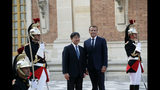 Japan's Crown Prince Naruhito, center left, is greeted by French President Emmanuel Macron before a meeting at the Chateau de Versailles, west of Paris, Wednesday, Sept. 12, 2018. Japan's Crown Prince Naruhito is for a nine-day goodwill visit in France. (AP Photo/Christophe Ena)