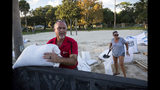Tybee Island residents Sib McLellan, left, and his wife, Lisa McLellan, load sandbags into the back of their truck while preparing for Hurricane Florence, Wednesday, Sept., 12, 2018, on Tybee Island, Ga. (AP Photo/Stephen B. Morton)