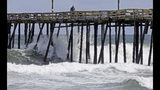 Waves crash under a pier in Kill Devil Hills, N.C., Wednesday, Sept. 12, 2018, as Hurricane Florence approaches the east coast. (AP Photo/Gerry Broome)