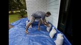 Stewart Thomason places sandbags that he used for previous hurricanes and tarp to prevent the flooding from rain at his home on the Isle of Palms,S.C. ahead of Hurricane Florence on Wednesday, Sept. 12, 2018. South Carolina Gov. Henry McMaster told reporters Wednesday that the storm could bring more rain to the state than 1989's devastating Hurricane Hugo. (Grace Beahm Alford/The Post And Courier via AP)