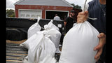 Seth Bazemore IV, center moves sandbags, Tuesday, Sept. 11, 2018, in the Willoughby Spit area of Norfolk, Va., as they make preparations for Hurricane Florence. (AP Photo/Alex Brandon)