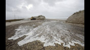Water passes though a breach in the dune line on Hwy 12 between Frisco and Hatteras Village, N.C., Friday, Sept. 14, 2018. (Steve Earley /The Virginian-Pilot via AP)