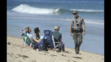 Cape Cod National Seashore Park Ranger Eric Trudeau walks up to a group of visitors on Newcomb Hollow Beach telling them that the beach is closed to swimming, Saturday, Sept. 15, 2018, in Wellfleet, Mass. Trudeau was walking up and down the beach alerting people to the beach closure after a Revere man was bitten and died from a shark bite Saturday off Newcomb Hollow Beach. (Merrily Cassidy/The Cape Cod Times via AP)