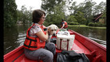 Susan Hedgepeth is assisted along with her dog Cooper by members of the U.S. Coast Guard in Lumberton, N.C., Sunday, Sept. 16, 2018, following flooding from Hurricane Florence. Hedgepeth was moved to higher ground. (AP Photo/Gerry Broome)