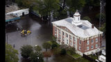 A backhoe moves through the streets inundated with floodwaters from Hurricane Florence in Trenton, N.C., Sunday, Sept. 16, 2018. (AP Photo/Steve Helber)