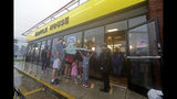 Luke Churchill, left, stands with his wife, Mary and their children, Katie, 13, Liam, 9, and Raighan, 3, as they wait in the rain outside an open Waffle House restaurant in Wilmington, N.C., after Hurricane Florence traveled through the area Sunday, Sept. 16, 2018. (AP Photo/Chuck Burton)