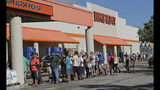 """FILE - In this Wednesday, Sept. 12, 2018 file photo, people line up outside a Home Depot for a new supply of generators and plywood in advance of Hurricane Florence in Wilmington, N.C. """"It's a year-round thing for us,"""" said Margaret Smith, spokeswoman for Atlanta-based Home Depot. """"When it's hurricane season, we are operating 24 hours a day."""" (AP Photo/Chuck Burton, File)"""