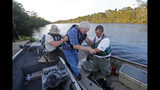William Larymore, right, of the South Carolina Department of Natural Resources, and Salvatore Cirencione, of the State Law Enforcement Division, help resident Franklin Bessemer, who lives on the river, onto the pier on the Waccamaw River in Conway, S.C., Monday, Sept. 17, 2018. Bessemer's boat had quit while he was checking on his home as residents evacuate. The river is expected to flood in the coming days due heavy rains from Hurricane Florence. (AP Photo/Gerald Herbert)