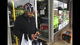 In this Sunday afternoon, Sept 16, 2018 photo, Mary Ingram checks the news on her phone outside a convenience store in Spring Lake, N.C, about a mile from where the Little River runs. Officials warn that the river is likely to pour from its banks and inundate towns in Cumberland County. Ingram lives just outside the mandatory evacuation zone, and was growing worried about the rising water. (AP Photo/Claire Galofaro)