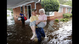 Bob Richling carries Iris Darden, 84, out of her flooded home as her daughter-in-law, Pam Darden, gathers her belongings in the aftermath of Hurricane Florence in Spring Lake, N.C., Monday, Sept. 17, 2018. (AP Photo/David Goldman)